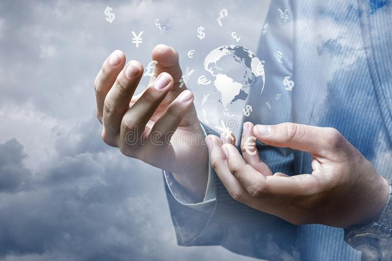 Businessman showing the hands of the global market for the currency . Businessman showing the hands of the global market for the currency against the sky royalty free stock images