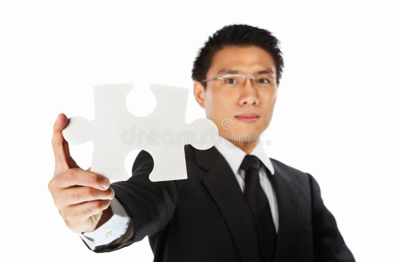 Businessman showing jigzaw puzzle piece. Asian businessman showing a piece of jigsaw puzzle, over white background royalty free stock image