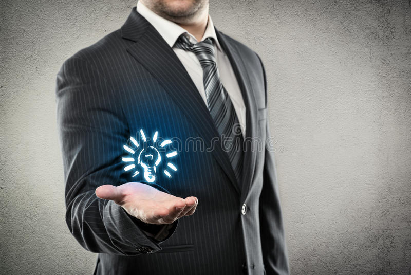 Businessman showing lamp. Young businessman holding bulb as a concept of new creative idea. Male in business suit sharing information and knowledge stock photo