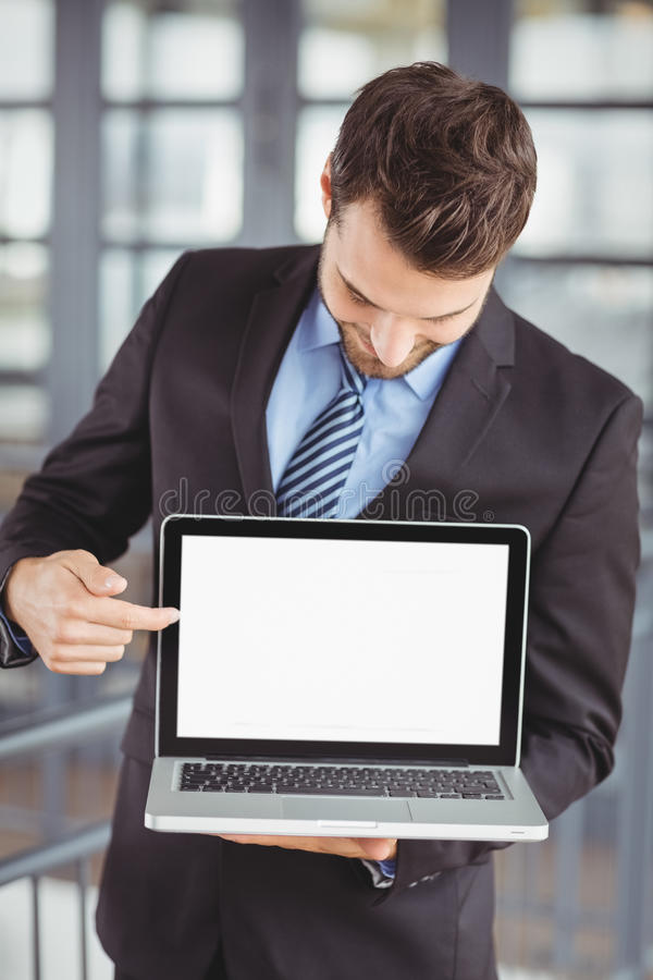 Businessman showing laptop in office. Businessman showing laptop while standing in office stock photos