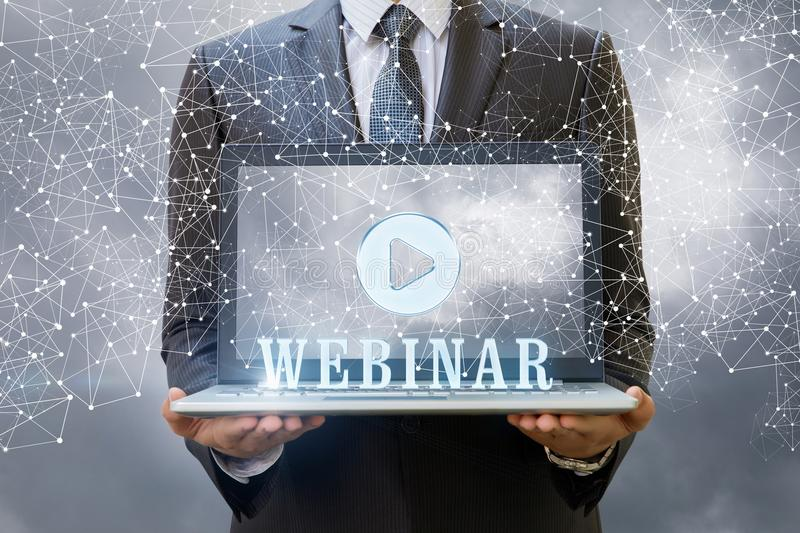 Businessman showing a laptop and the word webinar . stock images