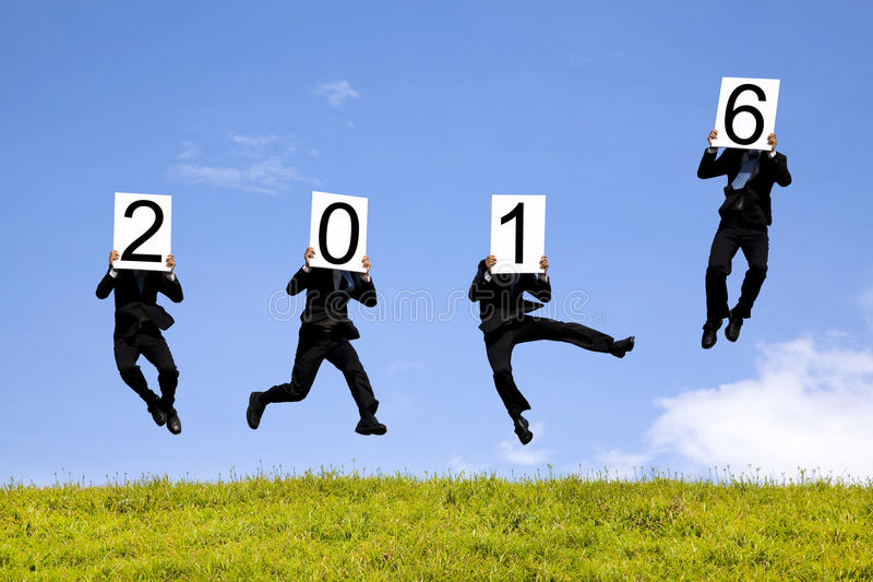 Businessman showing new year 2016. And jumping on the grass stock images