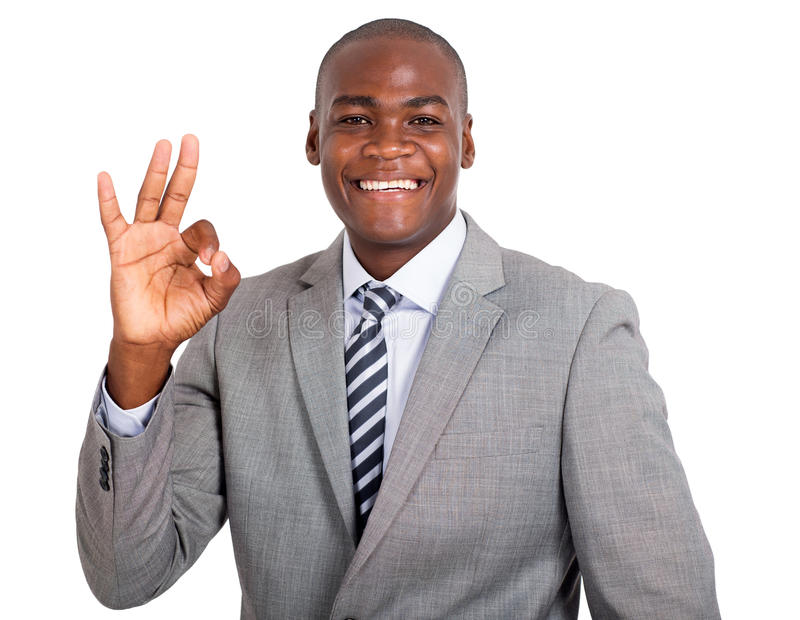 Businessman showing ok sign. Portrait of happy african businessman showing ok sign on white background royalty free stock photography