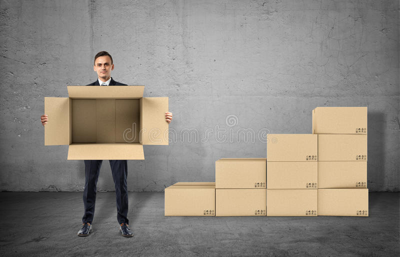 Businessman is showing an open box in his hands staying on gray background vector illustration