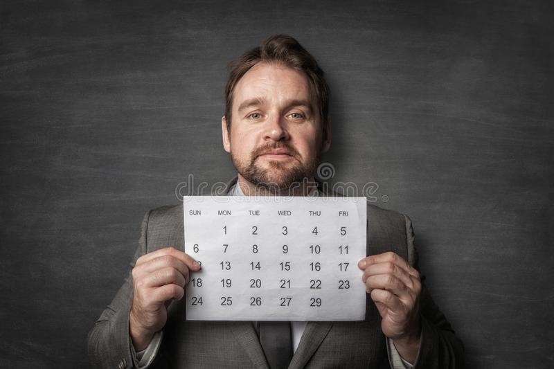 Businessman showing paper calendard in front of him royalty free stock image