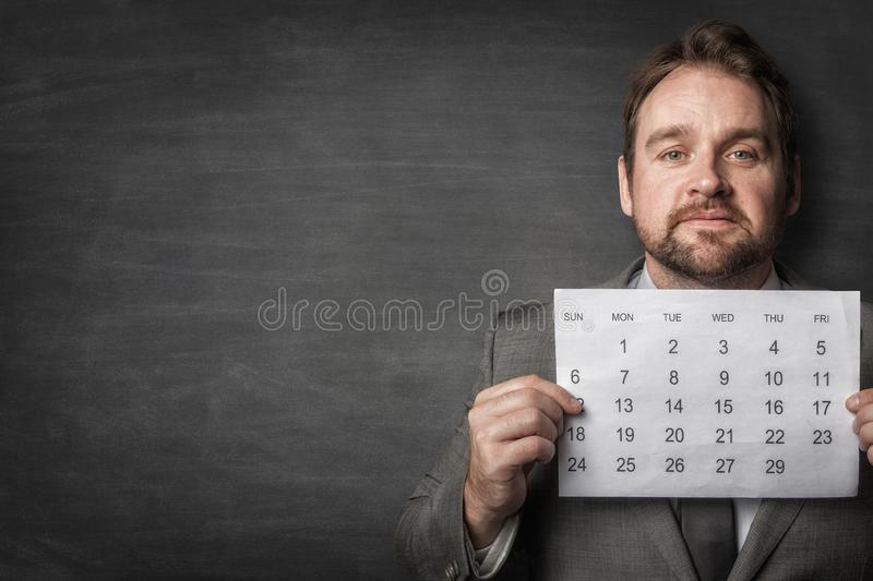 Businessman showing paper calendard in front of him royalty free stock photos