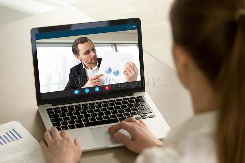 Businessman showing positive financial report via video call. Young businessman shows financial report via video call on laptop screen. Project manager royalty free stock image