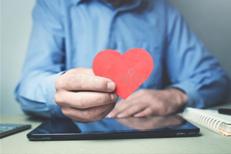 Businessman showing red heart. I love my job. royalty free stock photo