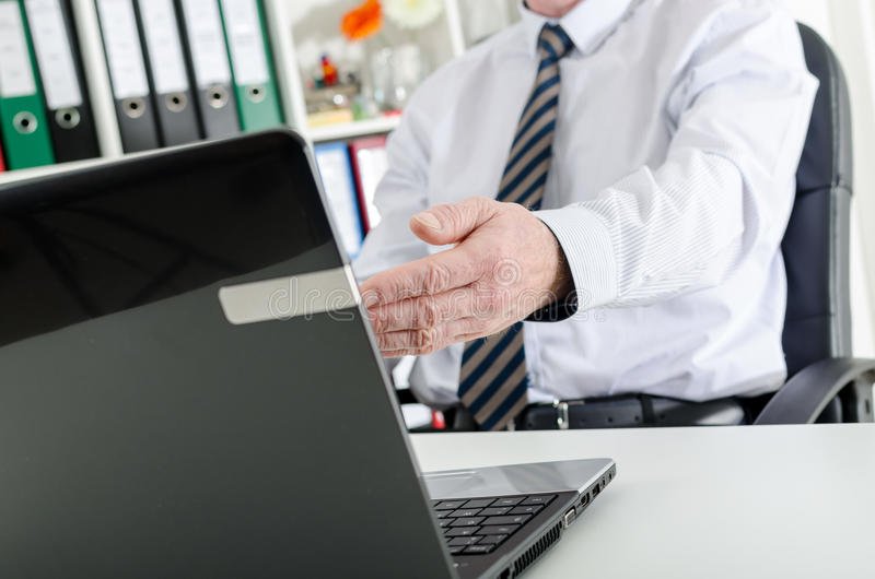 Businessman showing the screen of his laptop. At the office stock images