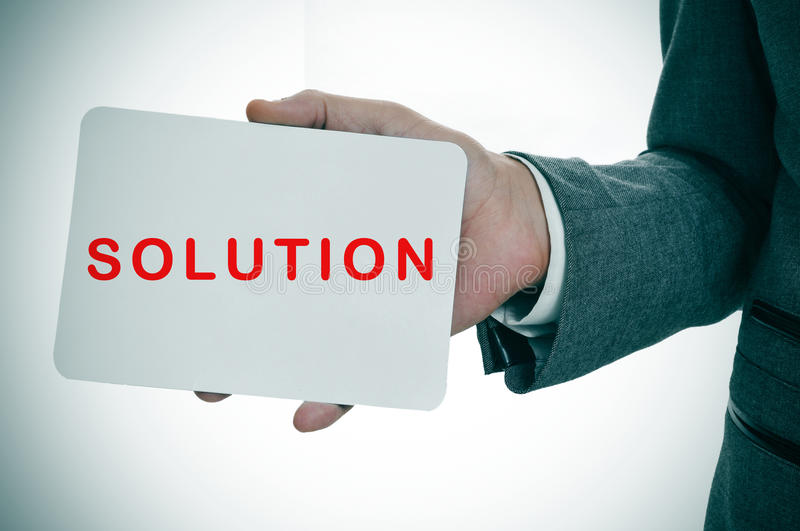 Businessman showing a signboard with the word solution royalty free stock images