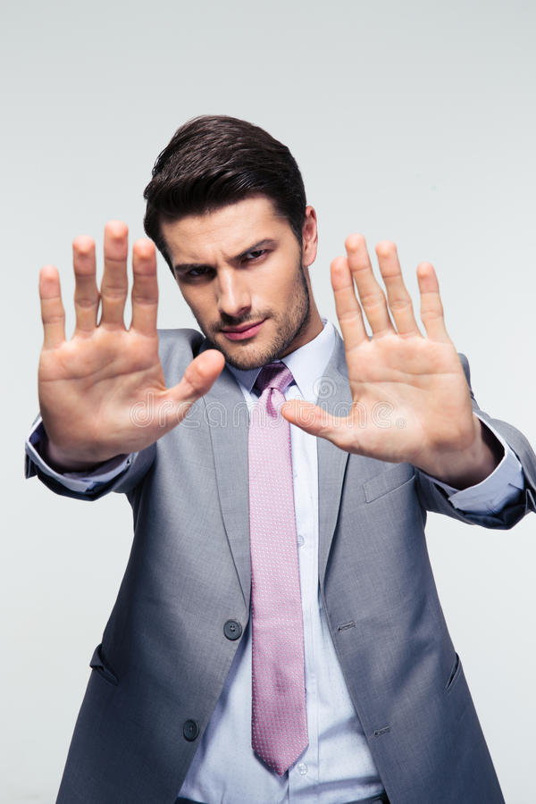 Businessman showing stop gesture. Over gray background. Looking at camera stock photography