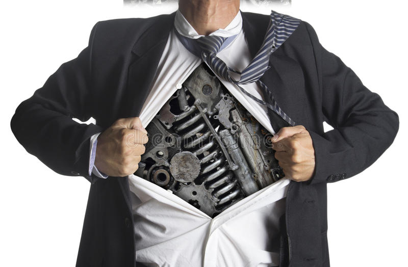 Businessman showing a superhero suit underneath machinery metal royalty free stock photo