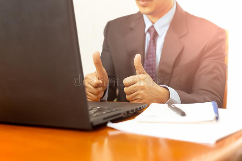 Businessman showing thumb up at workplace with laptop on the desk. stock photography