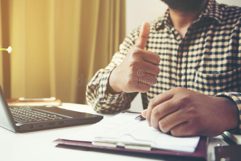 Businessman showing thumbs up in his workplace.Tump up concept royalty free stock photos