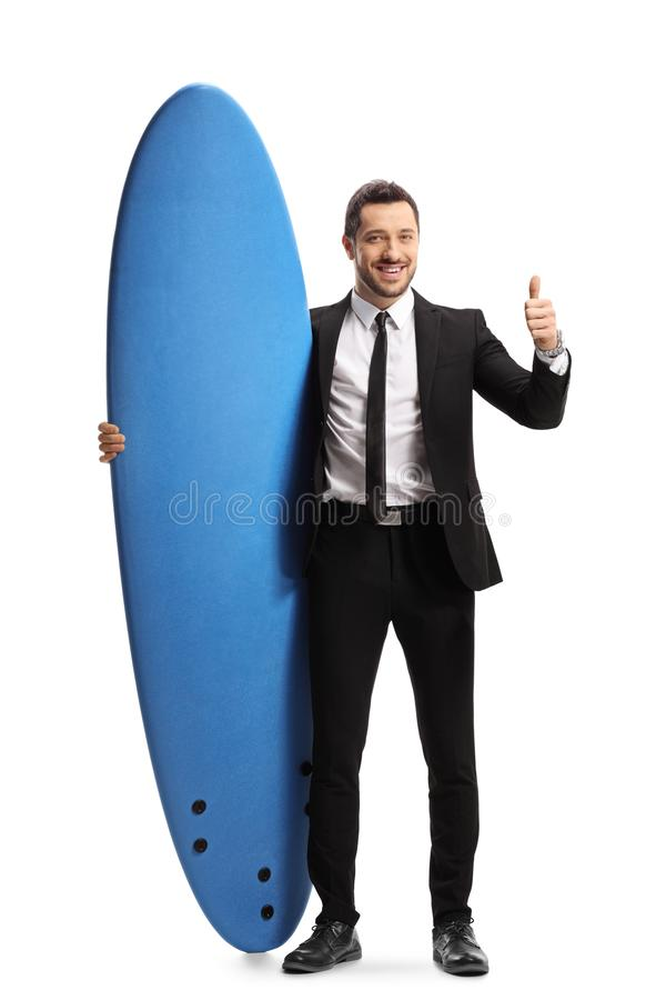 Businessman showing thumbs up and holding a surfing board. Full length portrait of a businessman showing thumbs up and holding a surfing board  on white royalty free stock photo