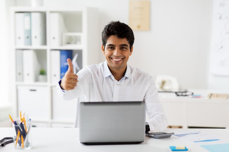 Businessman showing thumbs up at office. Business, people and technology concept - businessman with laptop computer showing thumbs up and papers at office stock photo