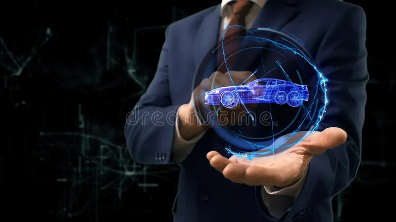 Businessman shows concept hologram Car on his hand. Man in business suit with future technology screen and modern cosmic background royalty free stock images