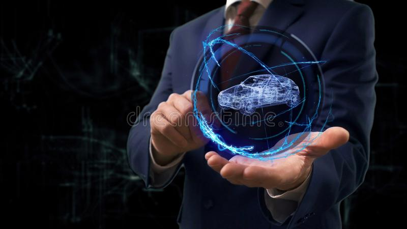 Businessman shows concept hologram 3d family car on his hand. Man in business suit with future technology screen and modern cosmic background stock image