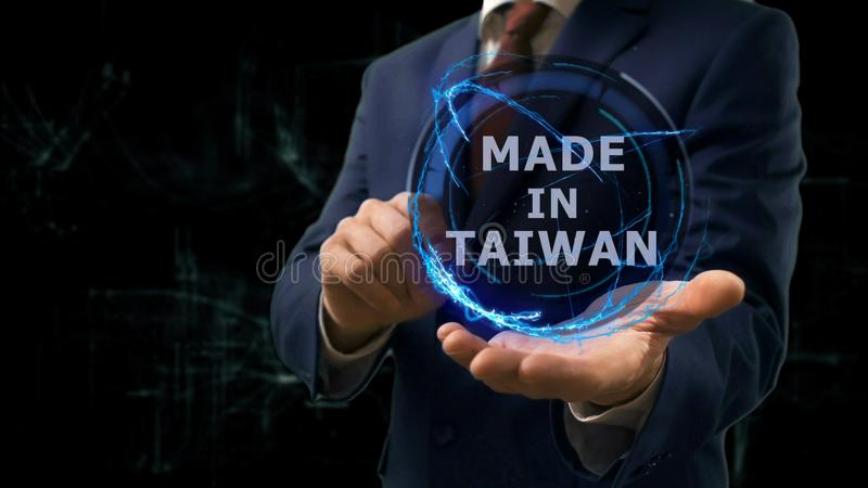 Businessman shows concept hologram Made in Taiwan on his hand. Man in business suit with future technology screen and modern cosmic background stock photo