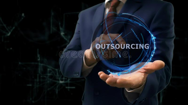 Businessman shows concept hologram Outsourcing on his hand. Man in business suit with future technology screen and modern cosmic background royalty free stock photo