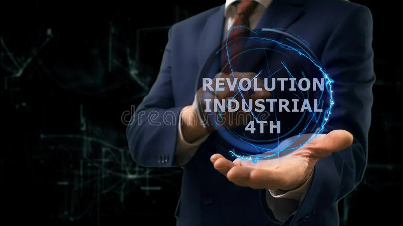 Businessman shows concept hologram Revolution Industrial 4th on his hand. Man in business suit with future technology screen and modern cosmic background stock photography