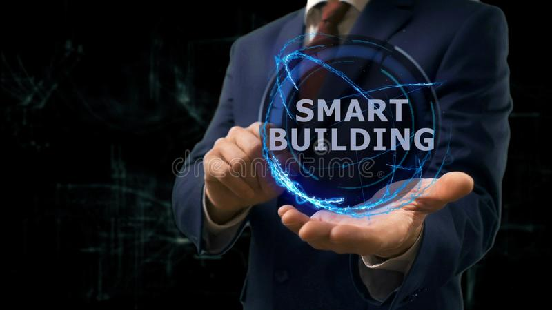 Businessman shows concept hologram Smart building on his hand. Man in business suit with future technology screen and modern cosmic background royalty free stock image