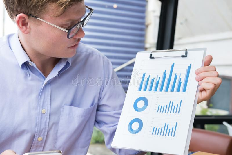 Businessman shows financial graph diagram at office. young man p. Resent investment chart at workplace. male entrepreneur shows business analysis report stock photography