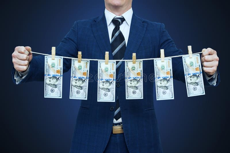Businessman shows laundered money. Businessman holding money hanging on a rope royalty free stock photo