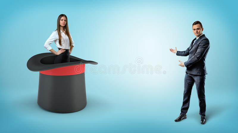 A businessman shows a self-assured businesswoman standing inside a giant illusionists hat on a blue background. royalty free stock images