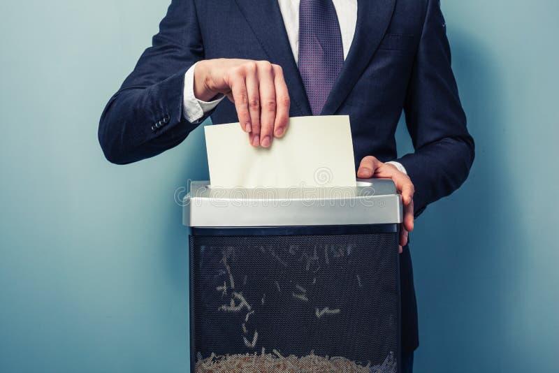 Businessman shredding documents stock photo