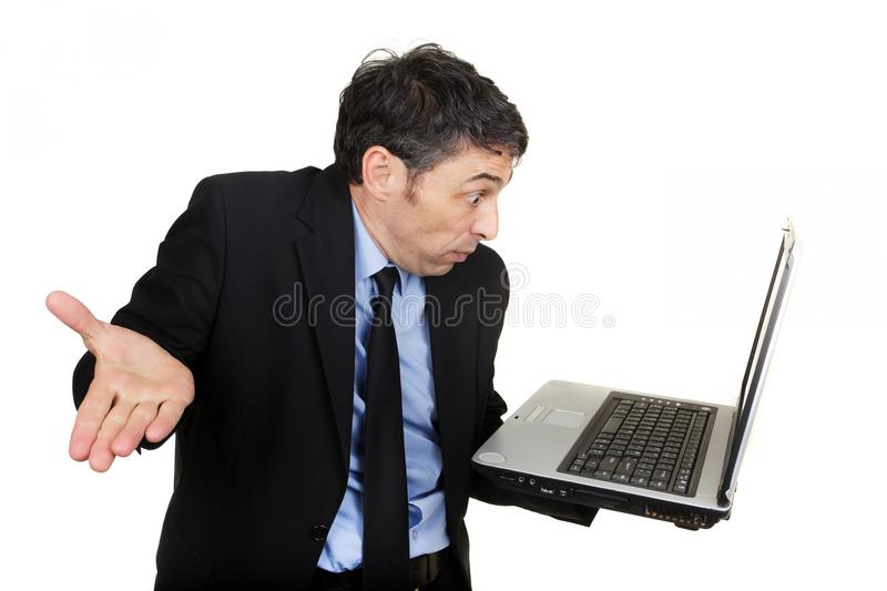Businessman shrugging as he reads his laptop. Businessman shrugging his shoulders and gesturing in disbelief or indifference as he reads his handheld laptop royalty free stock photography
