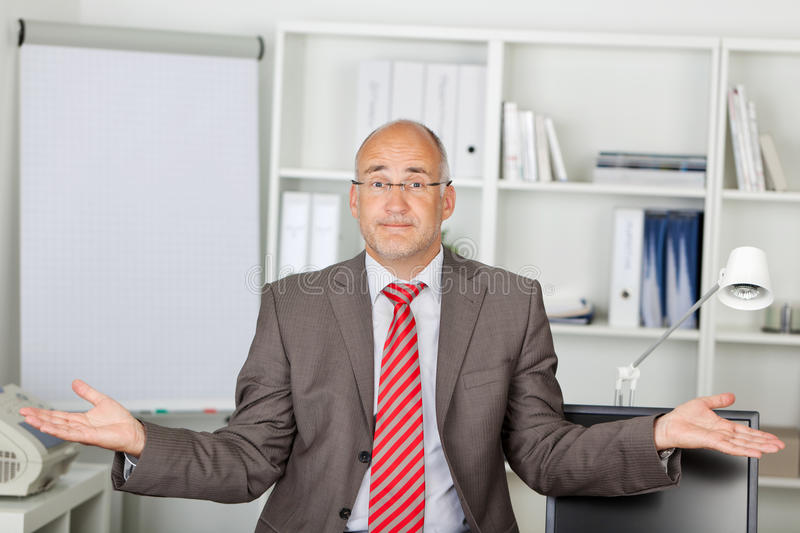 Businessman Shrugging Shoulders In Office. Portrait of mature businessman shrugging shoulders in office royalty free stock photo