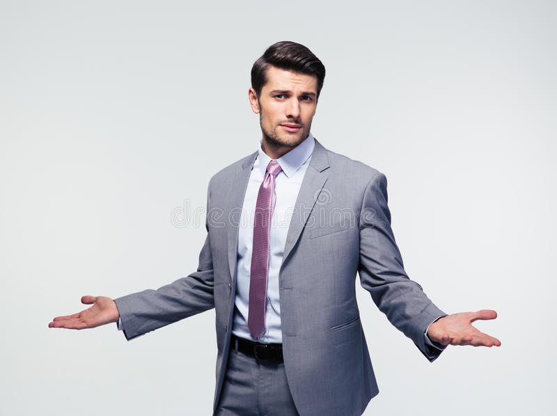 Businessman shrugging shoulders. Over gray background. Looking at camera stock images