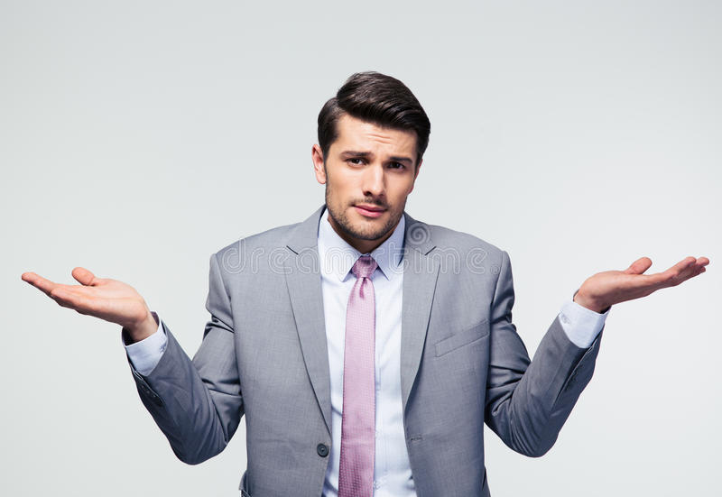 Businessman shrugging shoulders. Over gray background. Looking at camera stock photography