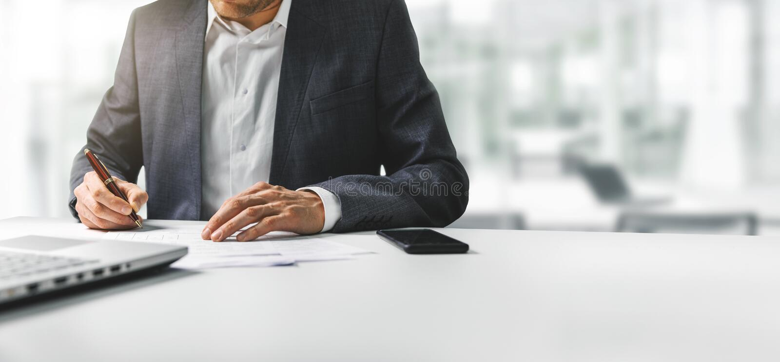 Businessman signing business contract papers in bright modern coworking office royalty free stock photo