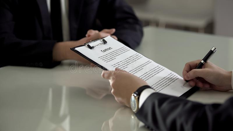 Businessman signing contract with partner, division of company shares, signature. Stock photo stock photo