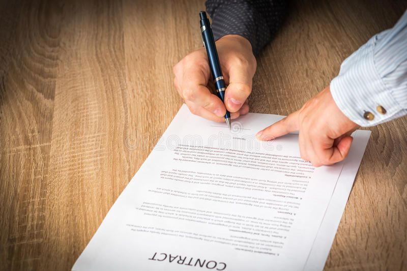 Businessman is signing a contract to conclude a deal. Business concept stock photo