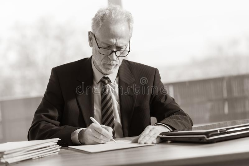 Businessman signing a document, black and white royalty free stock photo