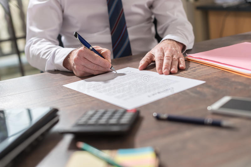 Businessman signing a document. In office royalty free stock photos