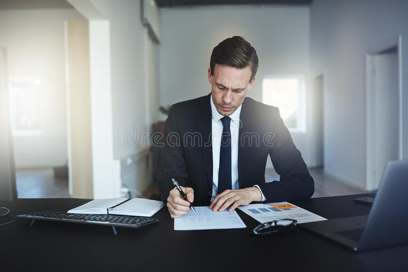 Businessman signing a document while working at his office desk. Focused businessman going over paperwork and signing documents while working at his desk in a stock images