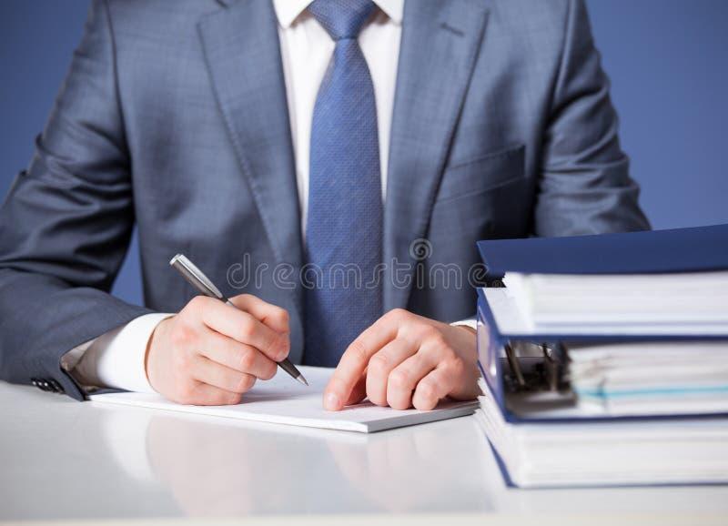 Businessman signing documents. Blue background stock photography