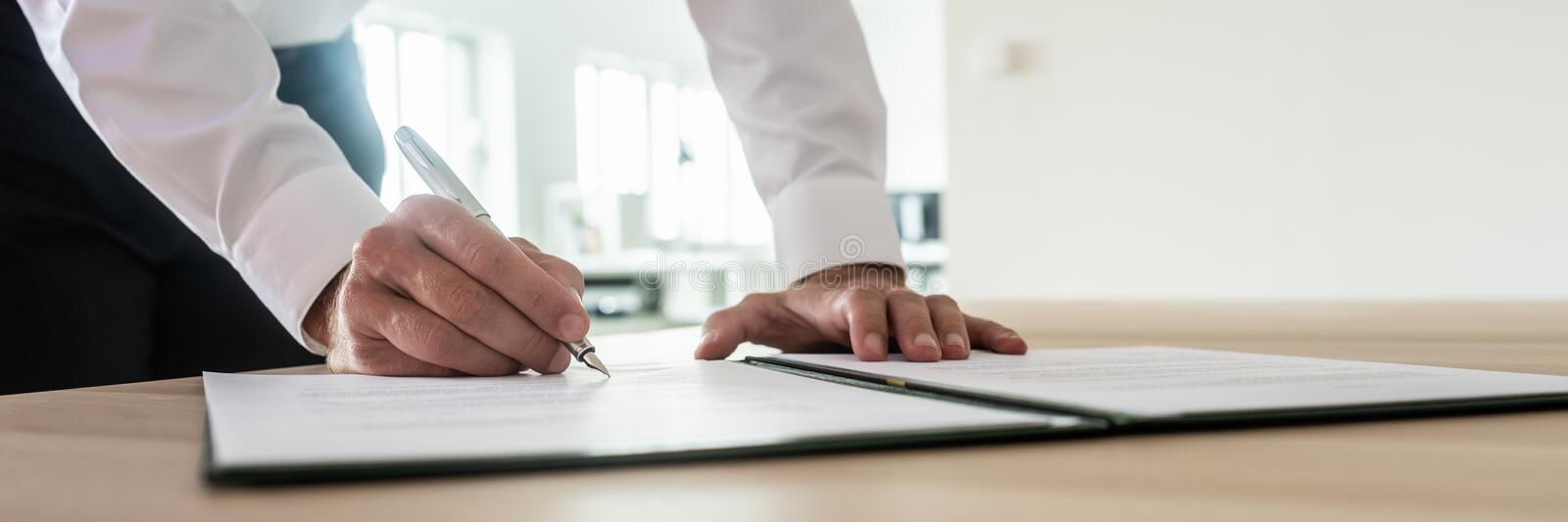Businessman signing important document. Panoramic image of businessman signing important document or contract while standing at his office desk royalty free stock image