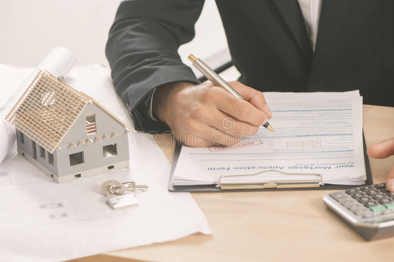 Businessman signing a mortgage contract royalty free stock image