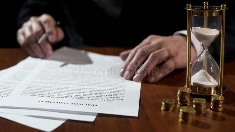 Businessman signing purchase agreement as time flows with sand in clock, closeup stock photography