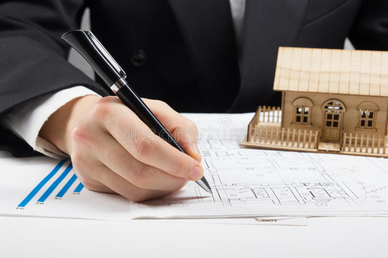 Businessman signs contract behind home architectural model.  royalty free stock photography