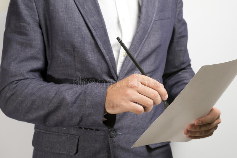 Businessman signs the document. Lawyer signs the document agreement, person in elegant business suit signs the document. On white background stock image