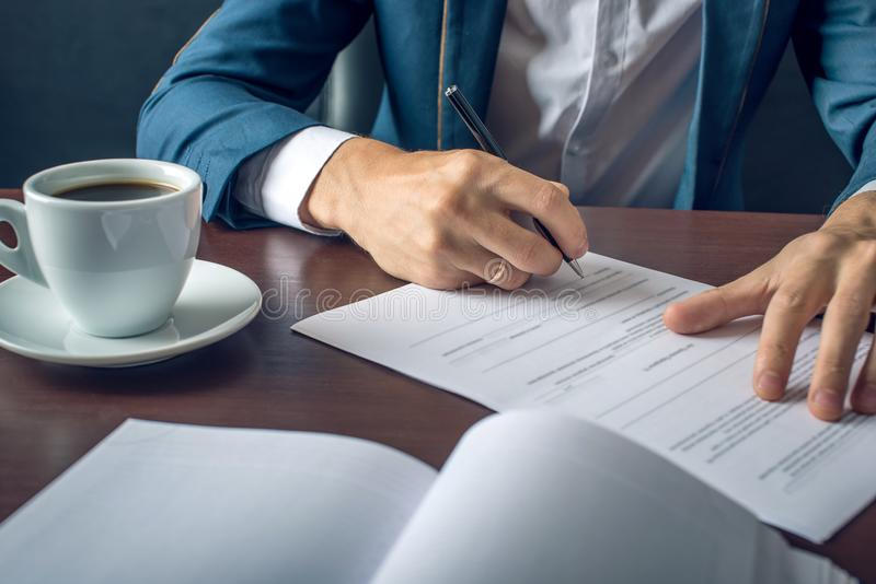 Businessman signs important legal documents on the desktop with Cup of coffee. Man businessman signs important legal documents on the desktop with Cup of coffee stock photography