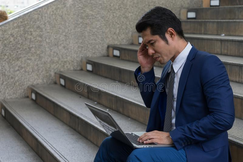 A businessman sit on the stairs and his hands clasped head, the feeling of stressed, sadness or displeasure. Caused by the non fulfillment of one`s hopes or stock photography