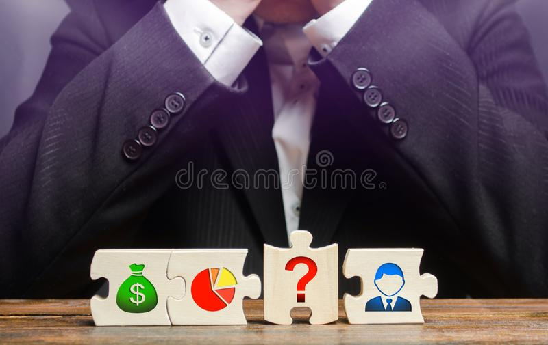 A businessman sits in despair because he is unable to set up a business processes. missing element. Wrong business model. Unprofitability, inefficiency. Failed stock photos