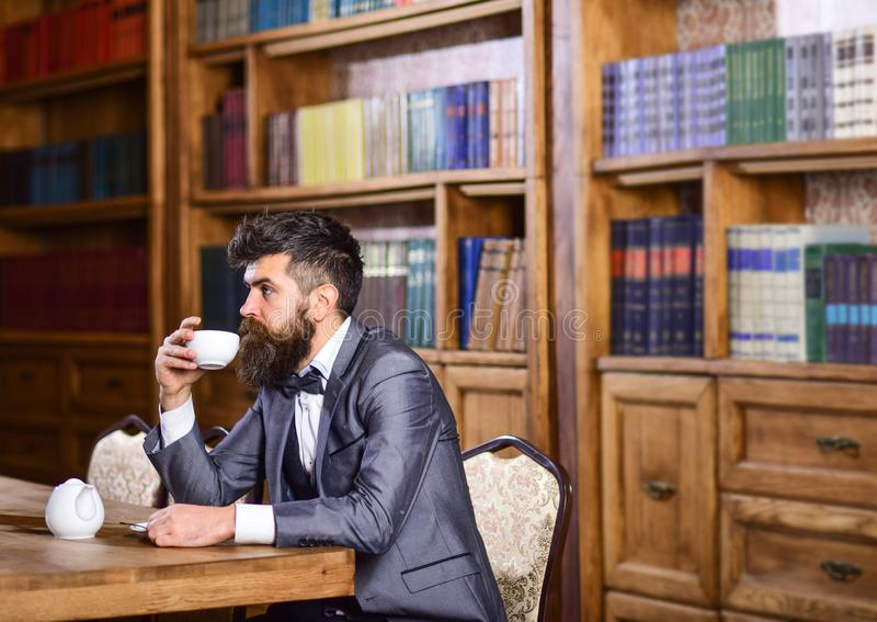 Businessman sits in vintage interior, holds book and cup of tea. Bearded man in luxury suit in his cabinet. Mature man with calm f royalty free stock photos